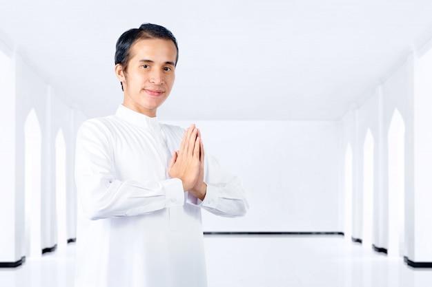 Homem muçulmano asiático em pé e orando