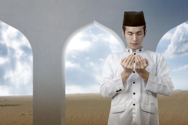 Homem muçulmano asiático em pé enquanto levanta as mãos e ora na mesquita