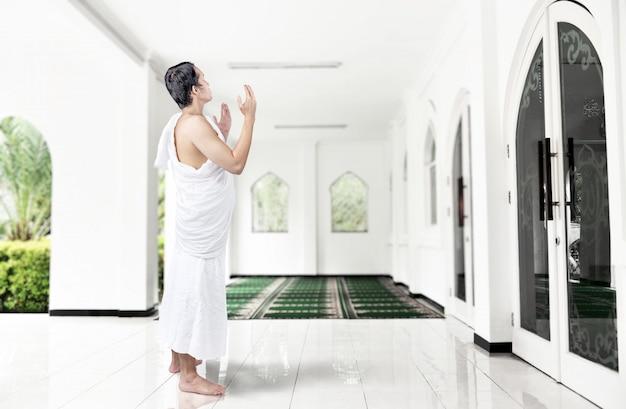 Homem muçulmano asiático em roupas ihram em pé e orando enquanto braços erguidos
