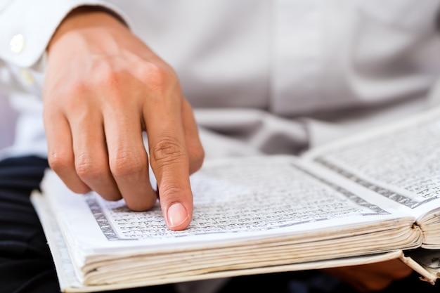 Homem muçulmano asiático estudando o alcorão ou o alcorão