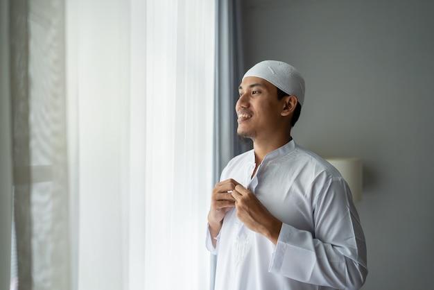Homem muçulmano asiático feliz em pé perto da janela e se vestir antes de ir para a mesquita