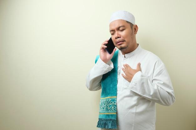 Homem muçulmano asiático fica triste ao receber notícias de seu smartphone