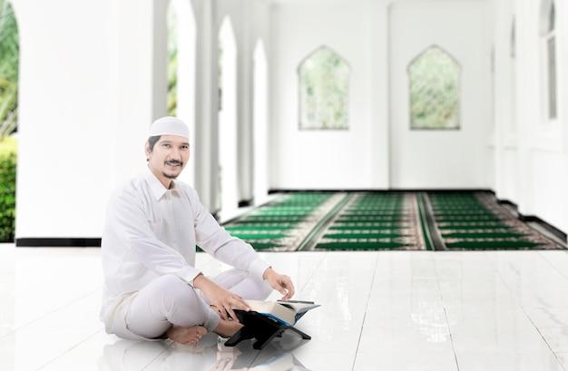 Homem muçulmano asiático sentado e lendo o alcorão na mesquita