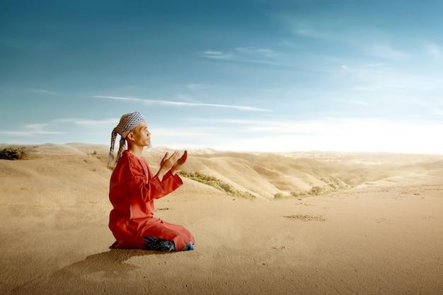 Homem muçulmano asiático sentado enquanto levantou as mãos e rezar