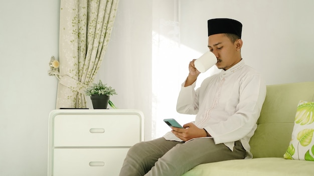 Homem muçulmano asiático termina a adoração tomando um drinque enquanto brinca em seu celular