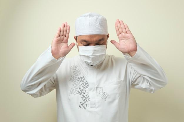 Homem muçulmano asiático usando máscara orando com um espaço vazio ao lado dele