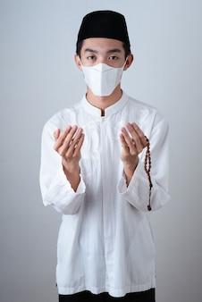 Homem muçulmano asiático vestindo roupas muçulmanas e segurando contas de oração com máscara médica
