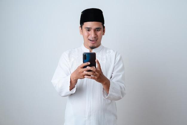 Homem muçulmano bonito vestindo roupas muçulmanas e segurando o telefone, batendo papo na parede branca