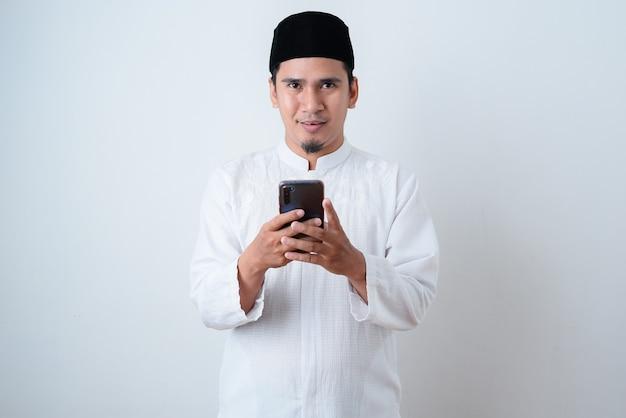 Homem muçulmano bonito vestindo roupas muçulmanas e segurando seu telefone olhando para a câmera na parede branca