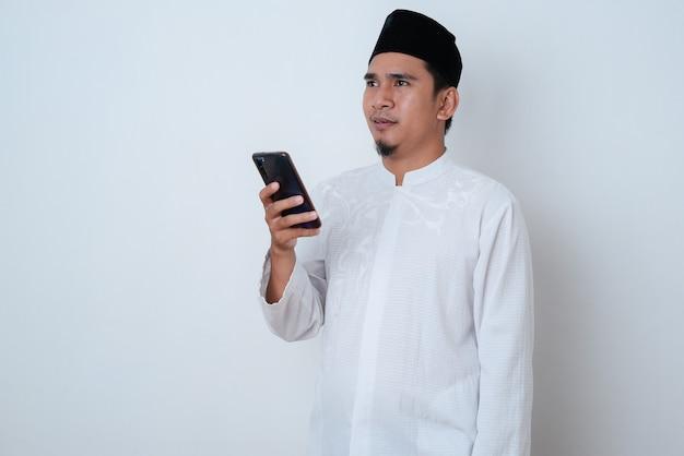 Homem muçulmano bonito vestindo roupas muçulmanas e segurando seu telefone, olhando para o outro lado na parede branca
