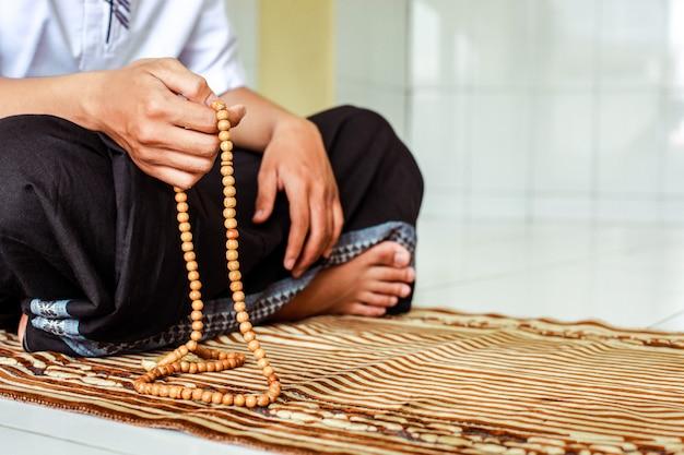 Homem muçulmano com as mãos segurando um rosário para contar dzikir