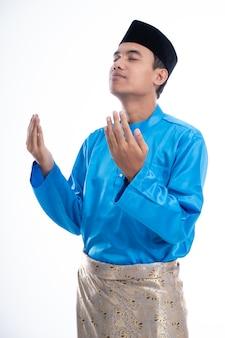 Homem muçulmano com boné de cabeça orando a deus