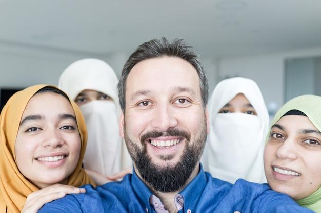 Homem muçulmano com retrato de 4 mulheres