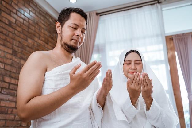 Homem muçulmano e mulher rezando de braço aberto