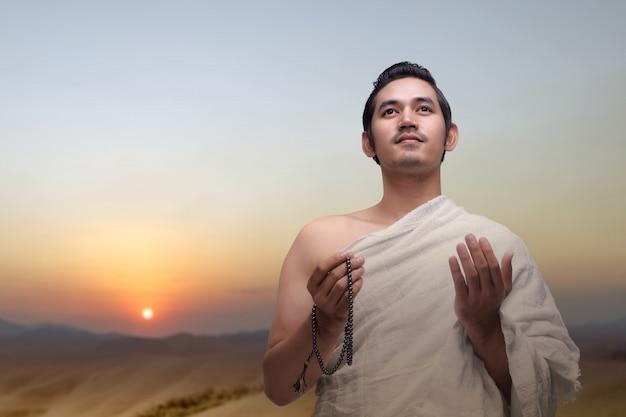 Homem muçulmano em roupas ihram rezando com contas de oração nas mãos