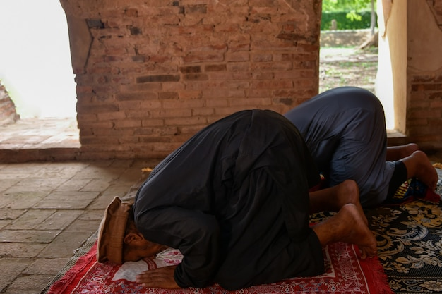 Homem muçulmano está rezando em uma antiga mesquita na tailândia.