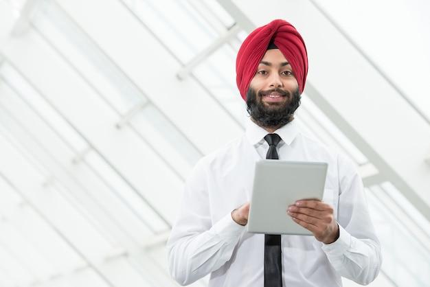 Homem muçulmano fica com um tablet e olha para algo.