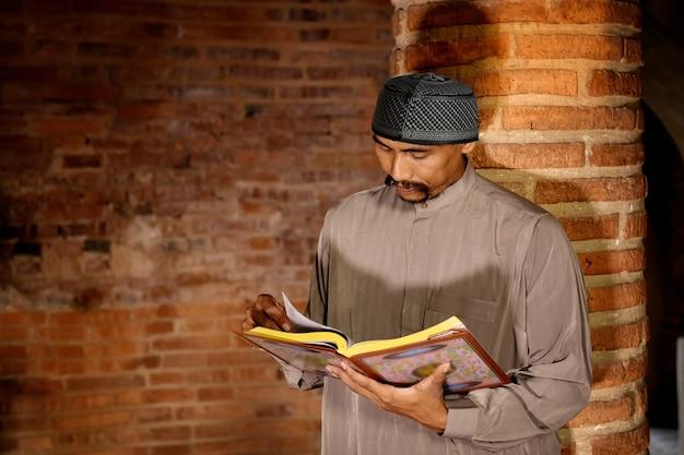 Homem muçulmano lendo o alcorão em uma antiga mesquita na província de ayutthaya, tailândia.