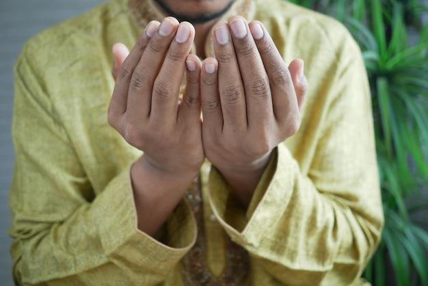 Homem muçulmano mantendo a mão em gestos de oração durante o ramadã de perto