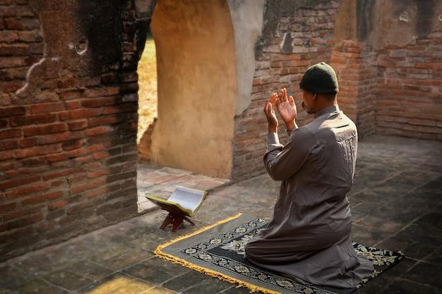 Homem muçulmano orando em uma antiga mesquita na província de phra nakhon si ayutthaya, tailândia, muçulmanos asiáticos
