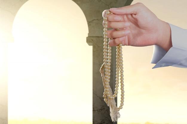 Homem muçulmano rezando com contas de oração nas mãos