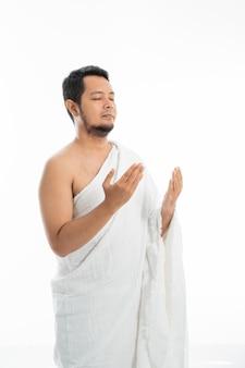 Homem muçulmano rezando em roupas brancas tradicionais