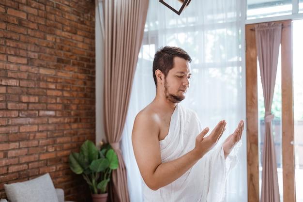 Homem muçulmano rezando vestindo roupas de ihram