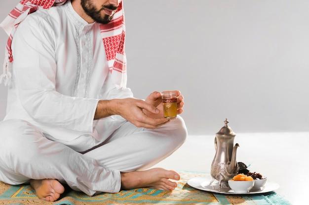 Homem muçulmano segurando uma xícara pequena de chá tradicional