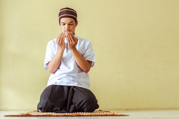 Homem muçulmano sentado a implorar com um gesto de mão no tapete de oração