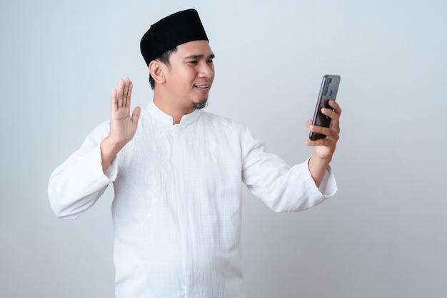 Homem muçulmano sorrindo, realizando uma videochamada para se comunicar com sua família durante o ramadã, em uma parede branca