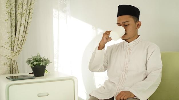 Homem muçulmano tomando um copo de bebida após o culto
