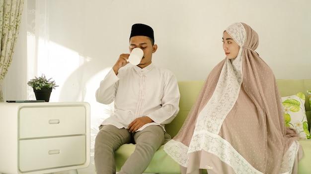Homem muçulmano tomando uma bebida com sua esposa