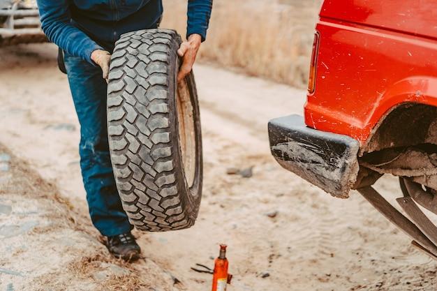 Homem mudar a roda manualmente em um caminhão 4x4 fora de estrada