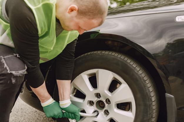 Homem mudar roda quebrada no carro