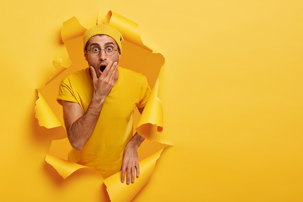 Homem mudo e aborrecido cobre a boca, encara com olhos arregalados, tem uma expressão em pânico, vestido com roupas casuais amarelas