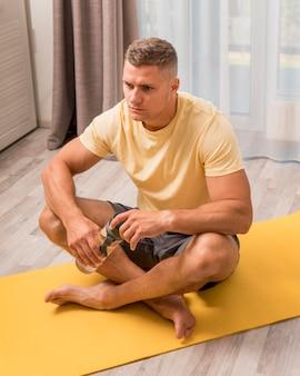 Homem muito apto a exercitar-se em casa no tapete