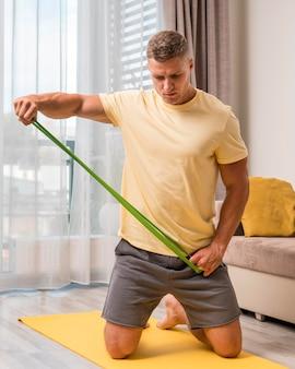 Homem muito apto a fazer exercício em casa com elástico