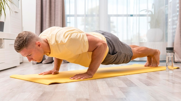 Homem muito apto a fazer exercício em casa no tapete com garrafa de água