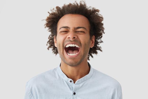 Homem muito feliz com cabelo encaracolado, ri feliz, mantém a boca bem aberta, mostra dentes brancos