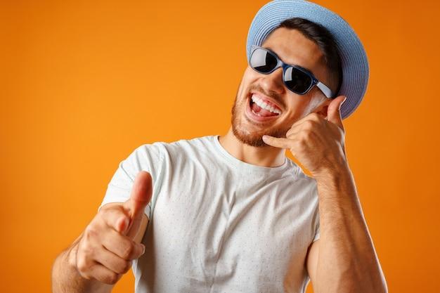 Homem muito feliz com chapéu de palha e óculos escuros mostrando um gesto de me ligar contra um fundo amarelo