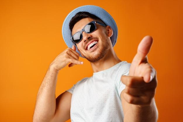 Homem muito feliz com chapéu de palha e óculos escuros mostrando um gesto de me ligar