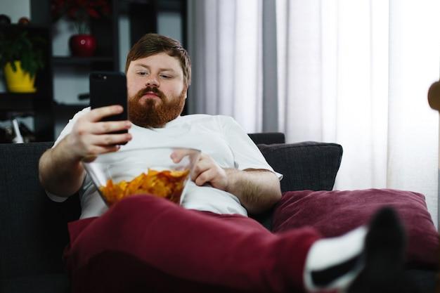 Homem muito gordo sorri verificando seu smartphone enquanto ele se senta no sofá e come