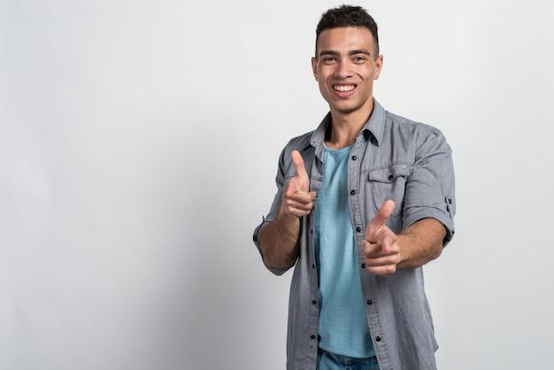Homem mulato feliz sorrindo e apontando para a câmera faz gesto de seus dedos