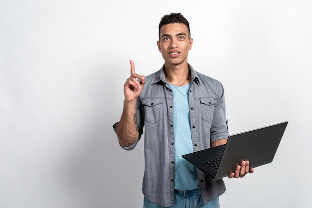 Homem mulato segurando um laptop nas mãos de pé
