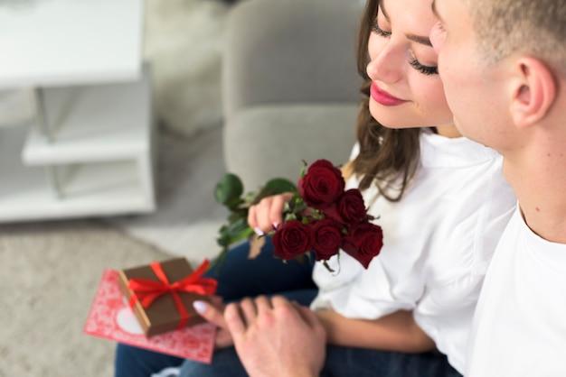 Homem, mulher abraçando, com, flores vermelhas, ligado, sofá