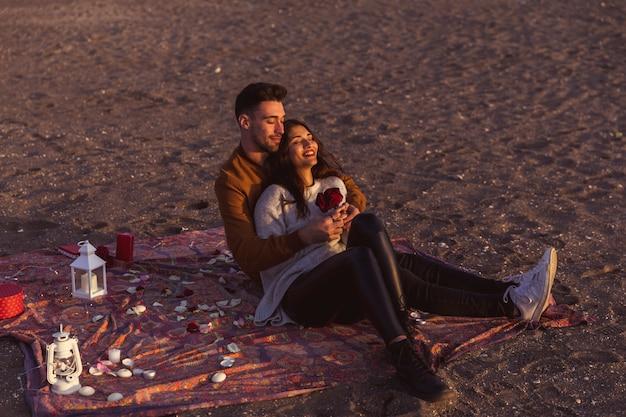 Homem, mulher abraçando, com, rosas, ligado, coverlet