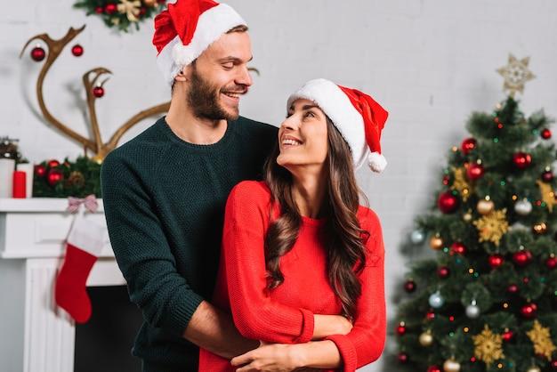 Homem, mulher abraçando, em, natal, chapéu
