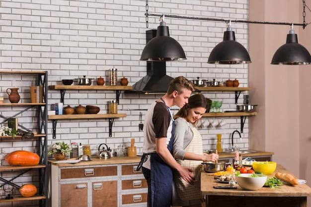 Homem, mulher abraçando, enquanto, cozinhar, junto