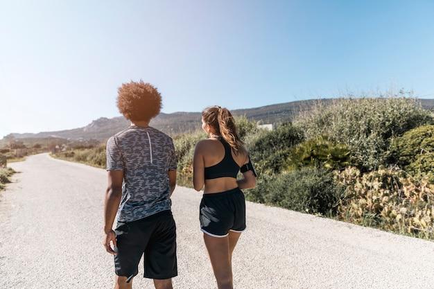 Homem mulher, em, sportswear, caminhando estrada