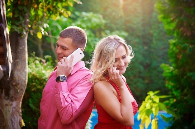 Homem mulher, em, vestido vermelho, conversa telefone, com, um ao outro